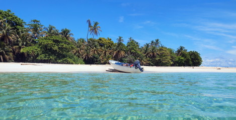 Pristine island sea shore with tropical vegetation and a boat landed on the beach, Caribbean sea, Panama