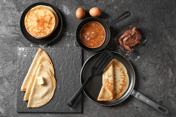 Composition with tasty thin pancakes and chocolate spread on table