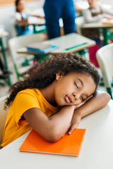 tired african american schoolgirl sleeping on desk during lesson