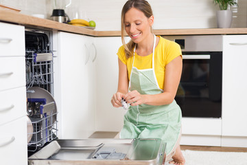 Smiling woman using dishwasher in the kitchen.