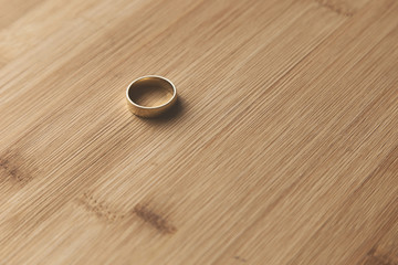 A gold ring on a wooden table top. This image can be used to represent marriage or commitment.