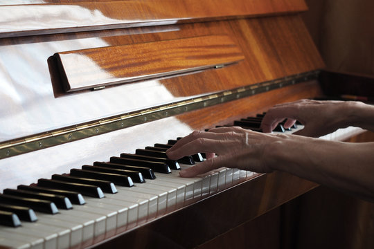 Elderly person hand playing the piano, close up