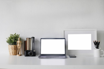Mockup Laptop on workspace and camera film, photo frame, book, jar of pencil with tree decoration office desk.