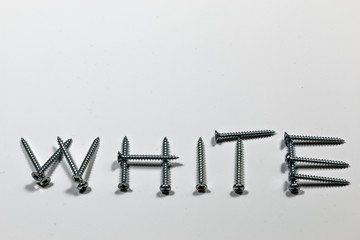The word white written with screws on a white background with reflections