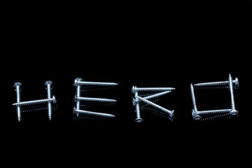 The word hero written with screws on a black background with reflections
