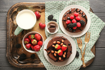 Tasty chocolate pancakes with berries and cup of milk on tray