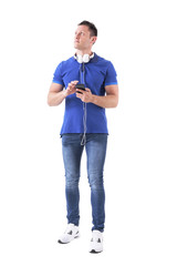 Thinking adult casual man with earphones attached to smartphone looking up. Full body isolated on white background.
