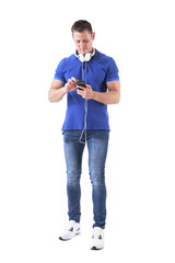 Adult casual man with headphones typing on smart phone touch screen searching for music. Full body isolated on white background.