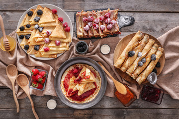 Composition with tasty thin pancakes, berries and jam on wooden table