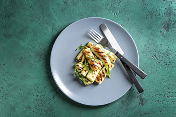 Plate with tasty grilled zucchini on color table