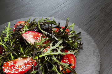 Authentic salad with arugula, tomatoes, sesame and olive oil on a black plate. Selected focus soft