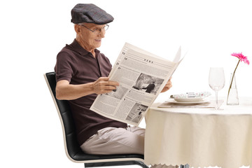 Senior seated at a restaurant table reading a newspaper