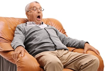 Terrified mature man sitting in an armchair