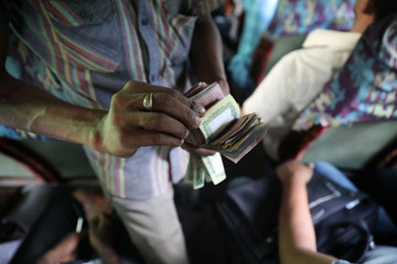 A driver's assistant collects fare from passengers of a bus in Dhaka