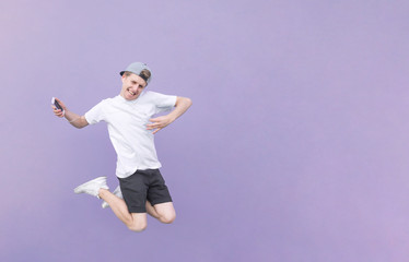 Portrait of a young man jumping with headphones and a smartphone on a pastel purple background. The teenager jumps with headphones in his ears and a smartphone in his hand