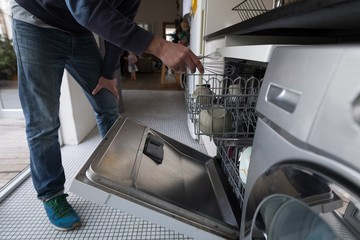 Man putting whisker inside the trolley in kitchen