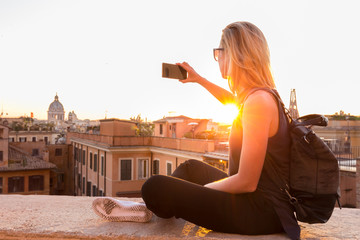 Female tourist with a fashinable vintage hipster backpack taking mobile phone photo of Piazza di Spagna, landmark square with Spanish steps in Rome, Italy at sunset.