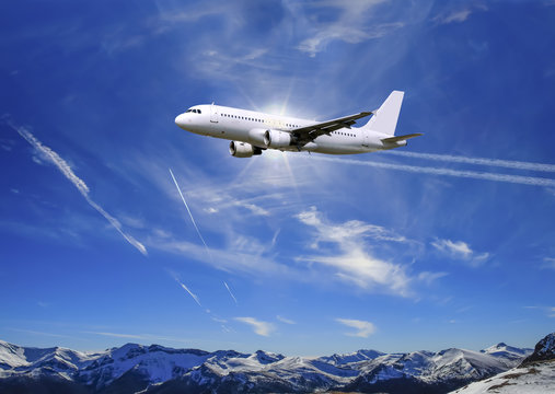 Airplane flying over sunny blue sky and Alpine mountains background