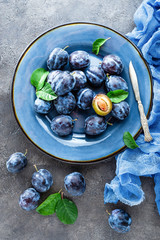 Fresh juicy sweet plums on plate with leaves