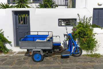 Motor tricycle with basket parked against whitewashed house.A three-wheeled blue motorcycle vehicle without people parked next to a white wall at Mykonos Town, on a sunny day.