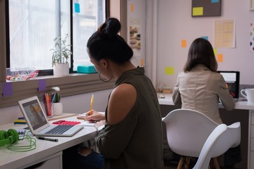 Fashion designers working on laptop in design studio