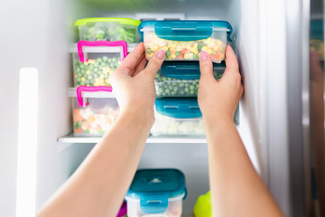 Woman placing container with frozen mixed vegetables in refrigerator.