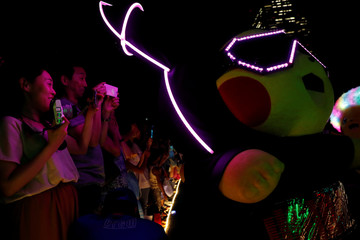 People take picture of a performer wearing Pokemon's character Pikachu costumes duirng a night parade in Yokohama