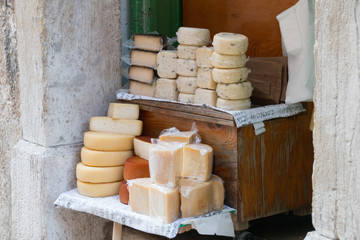 Truffle cheese and other cheeses are for sale in an alley.