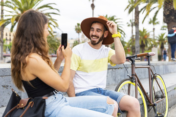 Spain, Barcelona, happy couple sitting on bench taking a smartphone picture