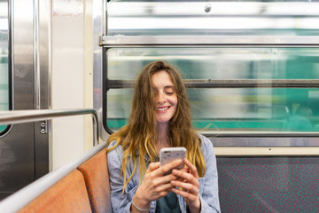 Portrait of smiling young woman in underground train looking at smartphone