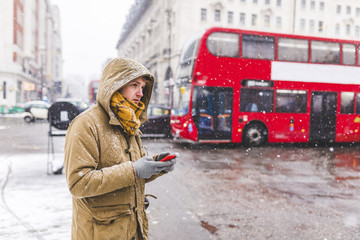 UK, London, young man with cell phone standing at roadside looking at distance