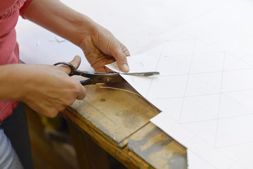 Close-up of woman cutting paper from draft in glazier's workshop