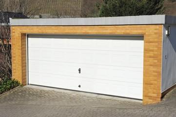 Garage mit Automatik-Tor und mit Klinker verblendeter Beton-Front in der Hauszufahrt