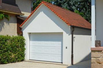 Beton-Garage mit Automatik-Tor, Satteldach, Dachrinne, Wasserfangkasten und Regenfallrohr in der Hauszufahrt