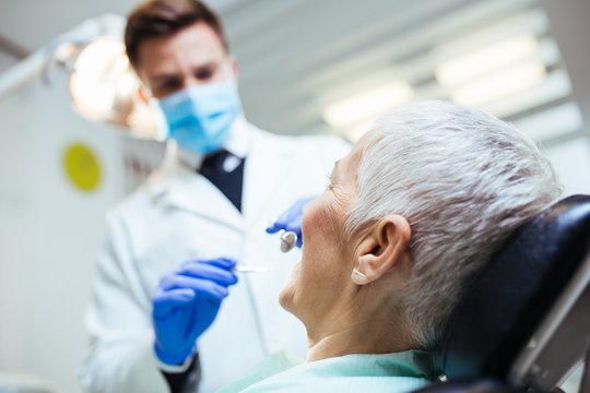 Beautiful senior woman having dental treatment at dentist's office.