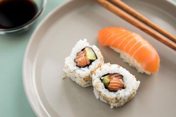 Lachs Nigiri und Inside Out California Sushi mit Avocado, Sojasauce und Holz Stäbchen auf Porzellan Teller