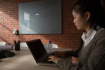Female executive using laptop in conference room
