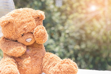 Teddy bear raised hand up against his face from hot sunlight on summer day.