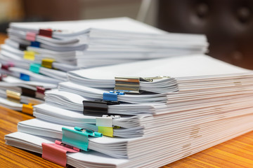Close up pile of unfinished paperwork on office desk waiting to be managed. Stack of homework...