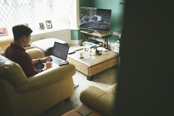 Man using laptop in living room