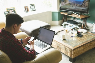 Man using laptop and mobile phone in living room
