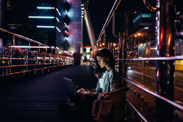 side view of young woman using laptop on street with night city lights on background Fotomurales