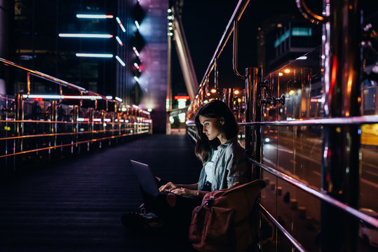 side view of young woman using laptop on street with night city lights on background