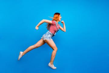 Wall Mural - Full-size portrait of running sporty girl in a striped T-shirt a