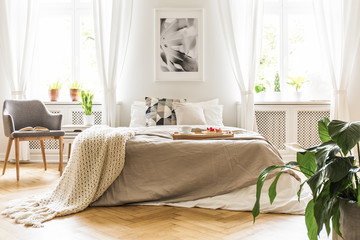 Open book on a gray, wooden armchair by a cozy bed with breakfast tray in a stylish bedroom interior with natural light coming through big windows