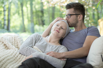 Husband kissing sick wife with cancer after chemotherapy