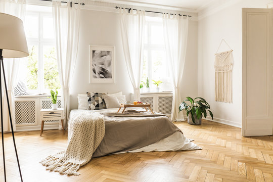 Framed poster on a white wall above a cozy double bed with beige sheets and breakfast tray in a spacious, sunny bedroom interior