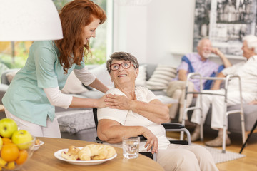 Friendly nurse supporting smiling senior woman in nursing house