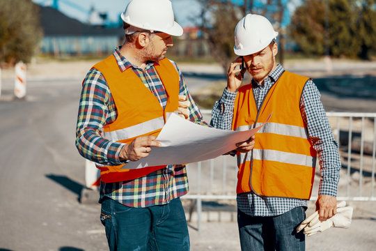 Worker and construction manager consulting project with engineer during road work