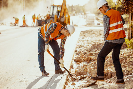 Workers in reflective vests using shovels during carriageway work
